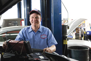 Image of Smiling AAMCO Mechanic repairing a Check Engine Light